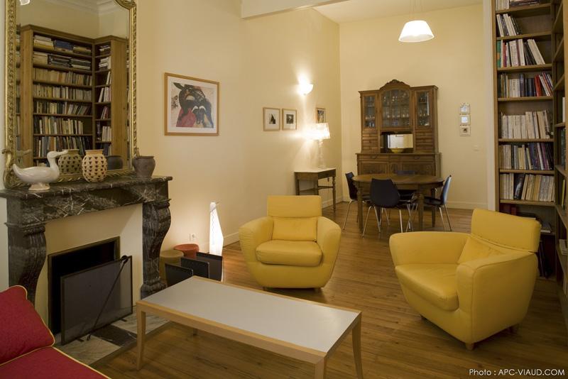 Salon chaleureux et convivial avec fauteuils jaunes, vaisselier en bois massif, table à manger, bibliothèque et cheminée