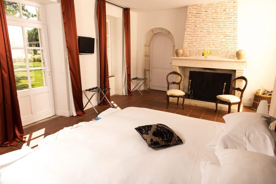 Chambre avec un lit double, une cheminée en pierres, une porte-fenêtre et une fenêtre avec des rideaux orangés, une télévision et la vue sur le jardin