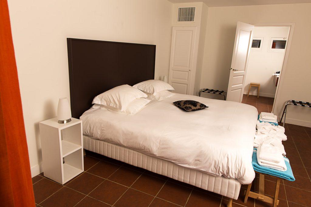 Grande chambre aux murs blancs avec un lit double entouré de tables de chevet et d'une salle d'eau dans le fond