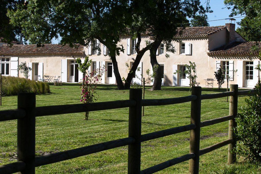 Une maison d'hôtes dans la campagne cachée derrière des arbres et une clôture de prairie