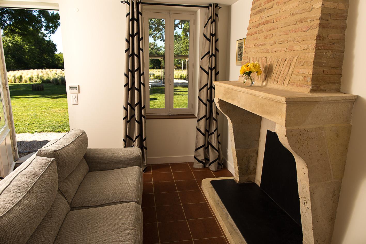 L'intérieur d'une chambre d'hôtes avec un canapé devant une cheminée et vue sur le jardin