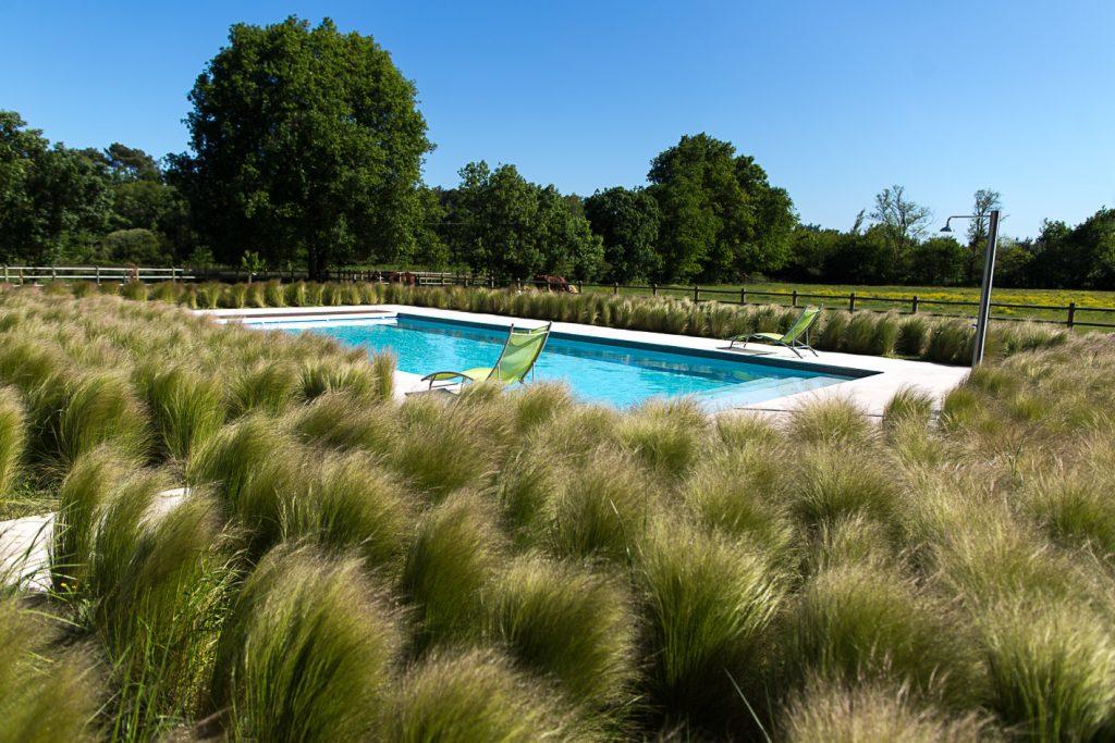 Grand jardin avec piscine extérieure en pleine nature et uGrand jardin avec piscine extérieure et un transat sous le soleil du Médoc sous le soleil
